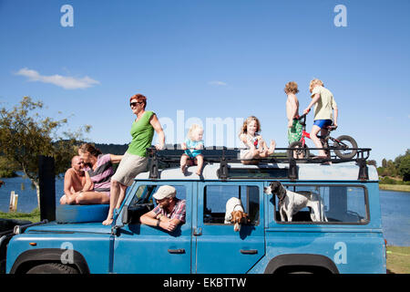 Family friends on top of off road vehicle, Lake Okareka, New Zealand - Stock Photo