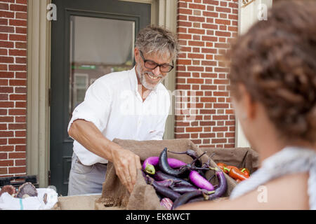 Farmer selling organic aubergines on stall - Stock Photo