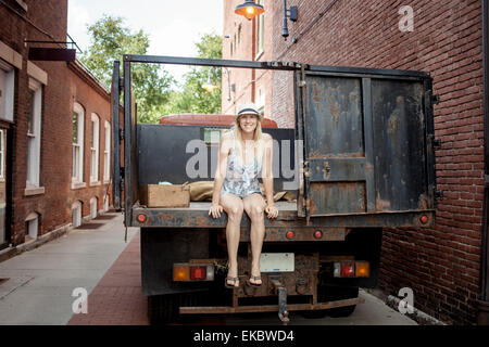 Woman sitting on a farmer's organic food truck outside grocery store - Stock Photo