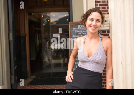 Portrait of female shop keeper in doorway of small store - Stock Photo
