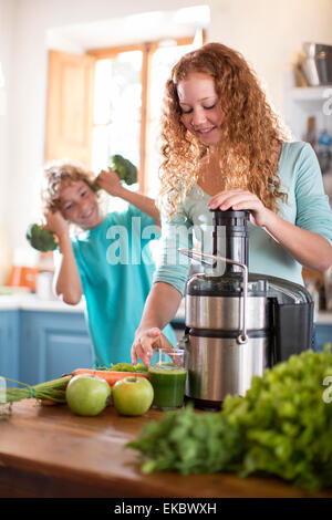 Sister blending fruit, brother playing with broccoli in background - Stock Photo