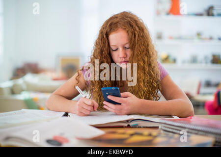 Teenage girl writing notes and using smartphone - Stock Photo