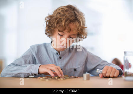 Teenage boy counting coins - Stock Photo