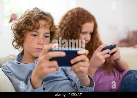 Siblings playing with handheld computer game on couch - Stock Photo