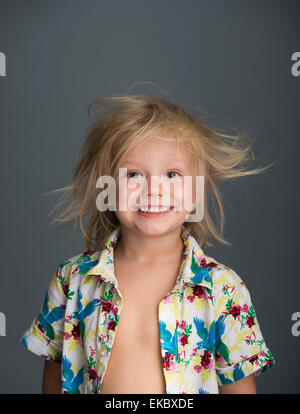 Portrait of young boy with messy hair, smiling - Stock Photo