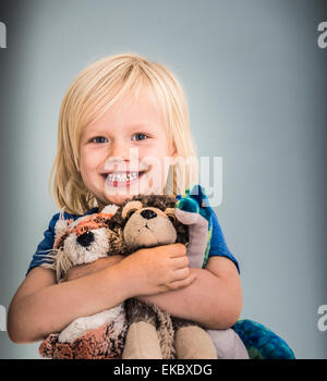 Portrait of young boy holding cuddly toys - Stock Photo