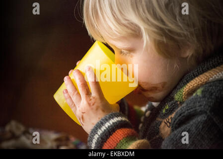 Portrait of young boy drinking from beaker - Stock Photo
