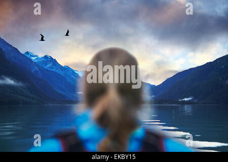 Rear view of female hiker gazing at seagulls and mountain lake, Haines, Alaska, USA - Stock Photo
