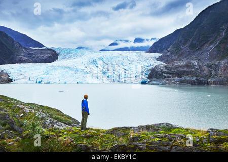 Male hiker gazing at Mendenhall Glacier, Juneau, Alaska, USA - Stock Photo