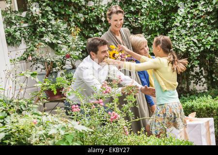 Mature couple greeting grandchildren in garden - Stock Photo