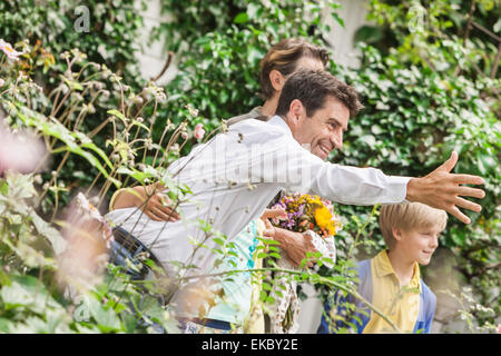 Mature couple greeting grandchildren in garden - Stock Photo
