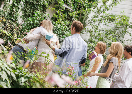 Mature couple greeting family in garden - Stock Photo