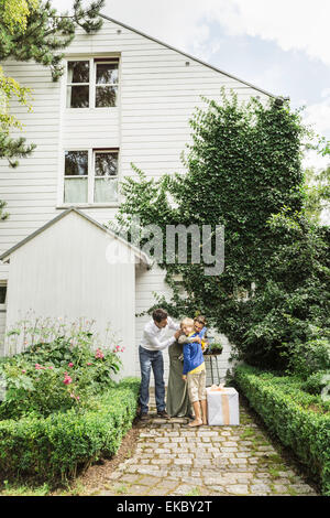 Mature couple greeting grandson in garden - Stock Photo