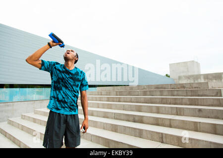 Young male runner drinking water on city steps - Stock Photo