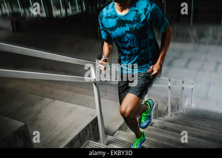 Young man running up city steps at night - Stock Photo