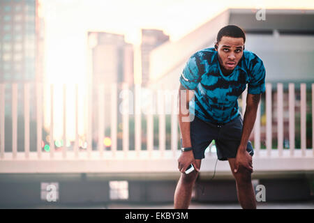 Young male runner taking a break on city roof in morning - Stock Photo