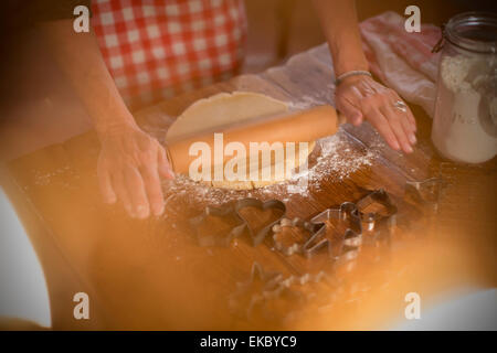 Rolling cinnamon and honey dough to make homemade cookies - Stock Photo