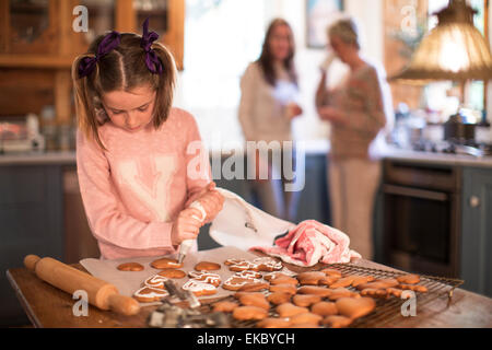 Girl icing homemade cinnamon and honey cookies - Stock Photo