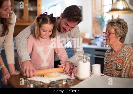 Father and daughter rolling dough to make homemade cookies - Stock Photo