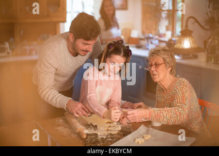 Three generation family cutting shapes in dough to make homemade cookies - Stock Photo