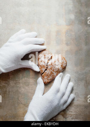 Gloved hands holding heart-shaped gingerbread cookie