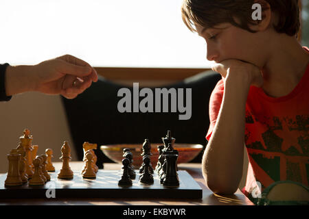 Father and son playing game of chess - Stock Photo