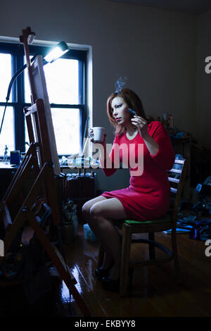 Mid adult woman sitting in front of easel, holding cigarette and hot drink - Stock Photo