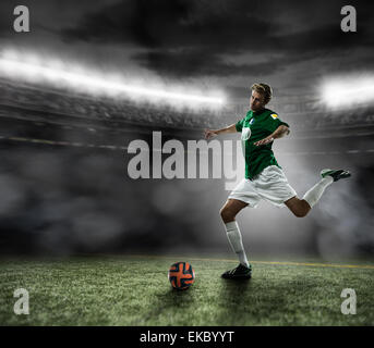 Footballer kicking ball - Stock Photo