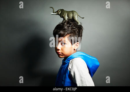 Boy with elephant ornament on top of head - Stock Photo