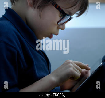 Close up of boy wearing eye glasses using touchscreen on digital tablet - Stock Photo