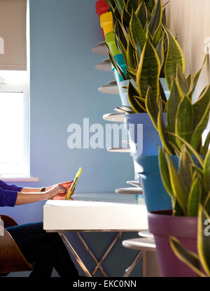 Cropped shot of woman using digital tablet in front of diagonal row of potted plants - Stock Photo