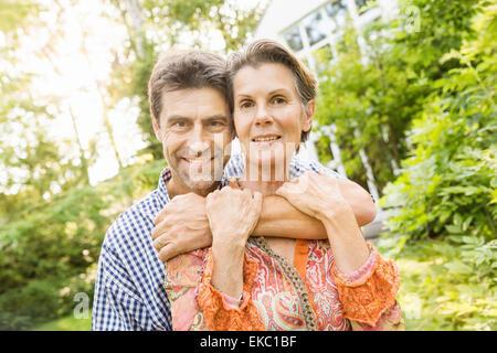 Couple hugging in garden - Stock Photo