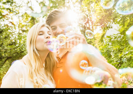Couple blowing bubbles in garden - Stock Photo