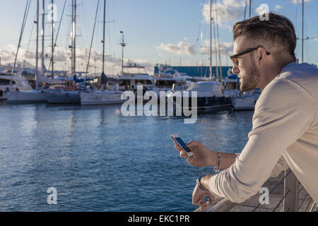 Young man using smartphone by port, Cagliari, Sardinia, Italy - Stock Photo