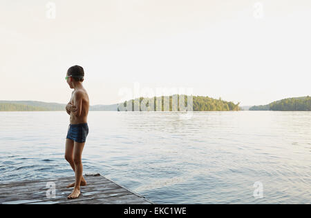 Boy looking out at lake from wooden pier, Ontario, Canada - Stock Photo