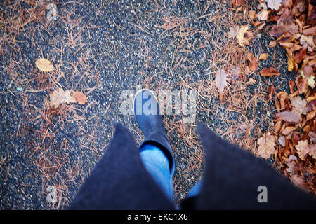 High angle view of woman in rubber boots strolling in autumn leaves - Stock Photo