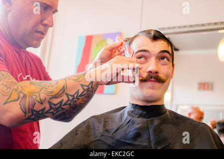 Young man with handlebar moustache having his hair cut - Stock Photo
