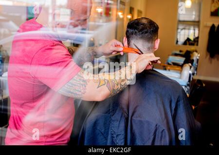 Young man having his hair cut - Stock Photo