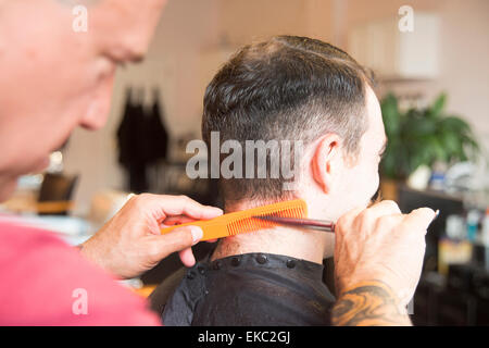 Young man having his hair cut - Stock Photo