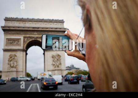 Woman taking photo of the Arc de Triomphe on phone, Paris, France - Stock Photo