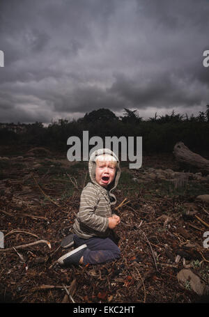 Young boy kneeling on ground crying against stormy sky - Stock Photo