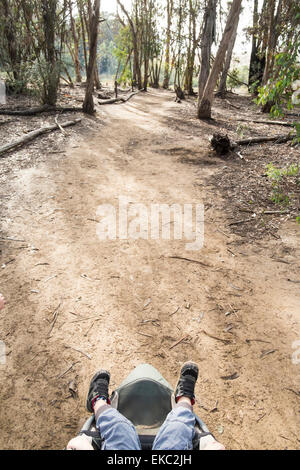 Boy's legs sticking out buggy in woods, overhead view