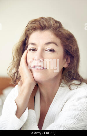 Portrait of mature woman resting hand on face - Stock Photo