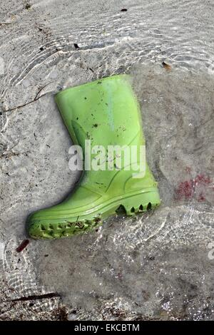 green boots trash on beach shore pollution - Stock Photo