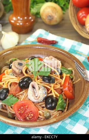 Spaghetti alla puttanesca with olives and anchovies on a napkin - Stock Photo