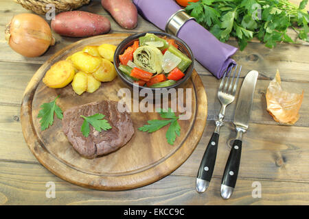 roasted ostrich steak with baked potatoes on a wooden board - Stock Photo
