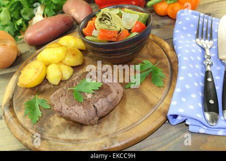 roasted ostrich steaks with baked potatoes and parsley on a wooden board - Stock Photo