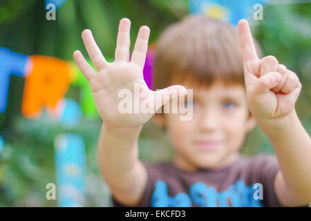 Birthday boy showing the number six with his hands - Stock Photo