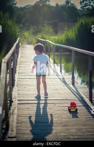 Boy pulling a toy truck across a bridge - Stock Photo