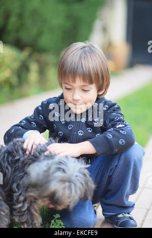 Young boy playing with a dog - Stock Photo